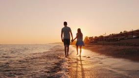 Broer en jongere zuster die volgens de brandingslijn op het strand bij zonsondergang lopen stock videobeelden
