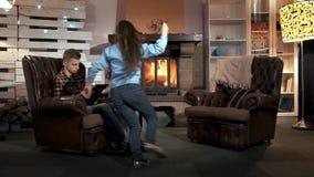 Broer en jongere zuster het besteden vrije tijd dichtbij de open haard in grote comfortabele woonkamer stock footage