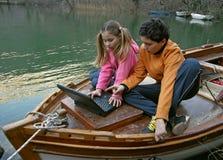 Broer en zuster aan boord met laptop stock afbeeldingen