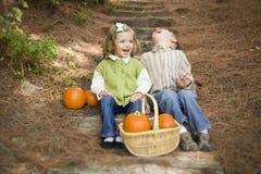 Broer en Zuster Children Sitting op Houten Stappen met Pompoenen Stock Afbeelding