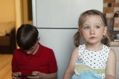 Broer en zuster in de keuken die en op de telefoon eten spelen stock fotografie