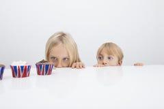 Broer en zuster die bij cupcakes op lijst staren Stock Foto's