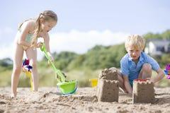Broer en zuster die bij strand zandkastelen maken royalty-vrije stock afbeelding