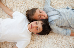 Broer en zuster die op de vloer liggen Stock Foto's