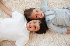 Broer en zuster die op de vloer liggen Royalty-vrije Stock Afbeeldingen