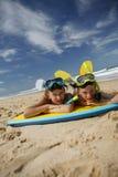Broer en zuster die op het zand liggen stock fotografie