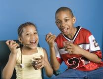 Broer en zuster die pudding eten stock foto