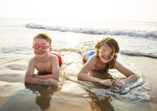 Broer en zuster die van het strand genieten stock foto