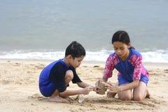 Broer en zuster die zandkasteel maken stock foto's