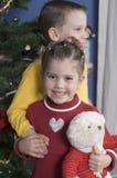 Broer en Zuster door een Kerstboom royalty-vrije stock afbeeldingen