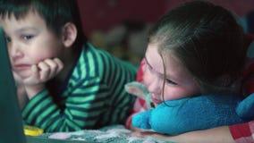 Broer en zuster het letten op video's op laptop en ik druk grote bewondering uit 4k close-up stock video