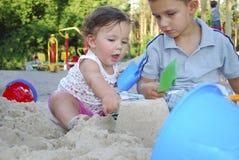 Broer en zuster het spelen in het zand op de speelplaats. Stock Foto