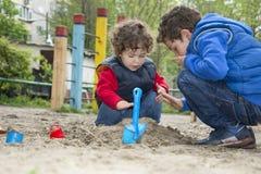 Broer en zuster het spelen in het zand op de speelplaats. Stock Afbeeldingen
