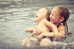Broer en zuster het spelen in het zwembad Stock Foto