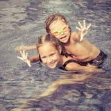 Broer en zuster het spelen in het zwembad Stock Afbeeldingen