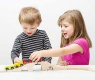 Broer en zuster het spelen met houten trein Stock Foto's