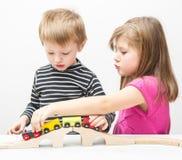 Broer en zuster het spelen met houten trein Stock Fotografie