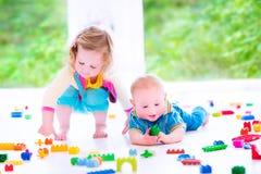 Broer en zuster het spelen met kleurrijke blokken Stock Afbeelding