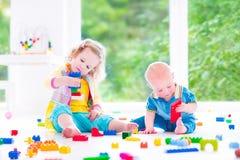 Broer en zuster het spelen met kleurrijke blokken Stock Afbeeldingen