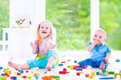 Broer en zuster het spelen met kleurrijke blokken Royalty-vrije Stock Foto's