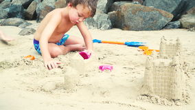 Broer en zuster het spelen met zand op een strand in Thailand stock footage