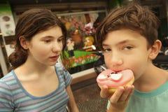 Broer en zuster met doughnut stock fotografie