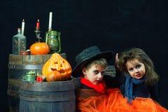 Broer en zuster op Halloween Grappige jonge geitjes in Carnaval-kostuums op donkere achtergrond stock fotografie