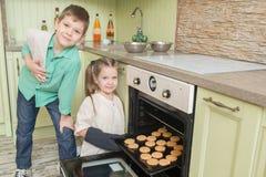 Broer en zusterbakselkoekjes in de oven in de keuken Royalty-vrije Stock Foto