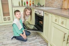 Broer en zusterbakselkoekjes in de oven in de keuken stock foto's