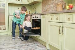 Broer en zusterbakselkoekjes in de oven in de keuken Stock Fotografie