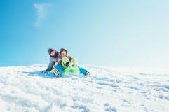 Broer en zusterdia neer van de zitting van de sneeuwhelling in  royalty-vrije stock foto's