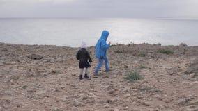 Broer en zustergang op de rotsen door het overzees stock videobeelden