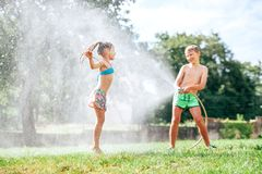 Broer en zusterspel samen met het water geven van slang in tuin stock afbeelding