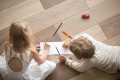 Broer en zustertekening met potloden op blad in ruimte stock afbeeldingen