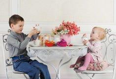 Broer en zusterzitting bij lijst met thee en decoratie Royalty-vrije Stock Foto