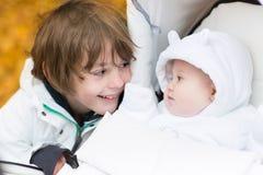 Broer het spelen met zijn zitting van de babyzuster in wandelwagen Royalty-vrije Stock Afbeelding