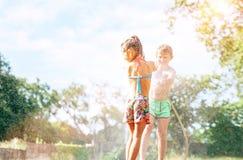 Broer sptays zijn water van de slittlezuster van tuinslang De kinderen hebben pret in hete de zomerdag stock foto