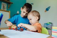 Broers die met stuk speelgoed auto's spelen Stock Afbeelding