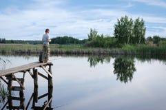 Broers die op de rivierbank vissen Jonge geitjes die met stokken in handen situeren stock foto's