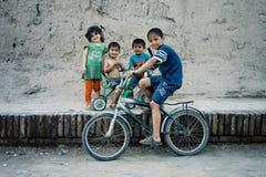 Broersans zusters met een fiets in de historische ommuurde stad van de zijdeweg stock fotografie