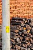 Brogować drewniane bele obok nieociosanego cegły ogrodzenia i oszczędnościowego słupa fotografia stock