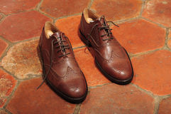 Brogue shoes. Brown leather brogue shoes on a rustic tile background Stock Images