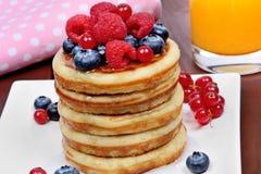 Brogujący bliny w talerzu z świeżymi jagodami i sokiem pomarańczowym na stole zdjęcia royalty free