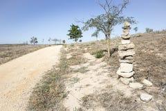 Brogujący kamienie na krawędzi drogi gruntowej na letnim dniu Obraz Stock