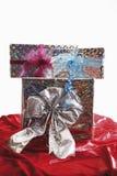 Brogujący prezenta pakuneczek na czerwonym aksamicie zdjęcie stock