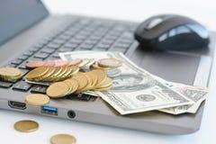 Broguje lub stos monety i dolarowi rachunki na laptop klawiaturze Zdjęcia Stock