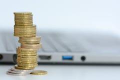 Broguje lub stos monety i laptop klawiatura Zdjęcie Stock