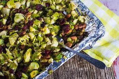 Broiled brussel sprouts with almonds and cranberries. Grilled brussel sprout entree or side dish with nuts and cranberries healhy food stock photos