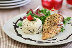 Broiled chicken breast. With wild rise and summer salad stock image
