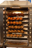 Broiled chicken at festival on Theresienwiese in Munich, 2015. Broiling machine with lots of chicken turning to get brown and ready to serve royalty free stock images